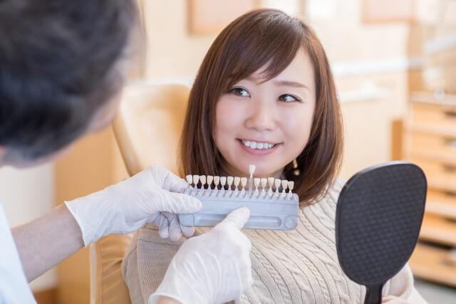 歯科医院でホワイトニングをする女性